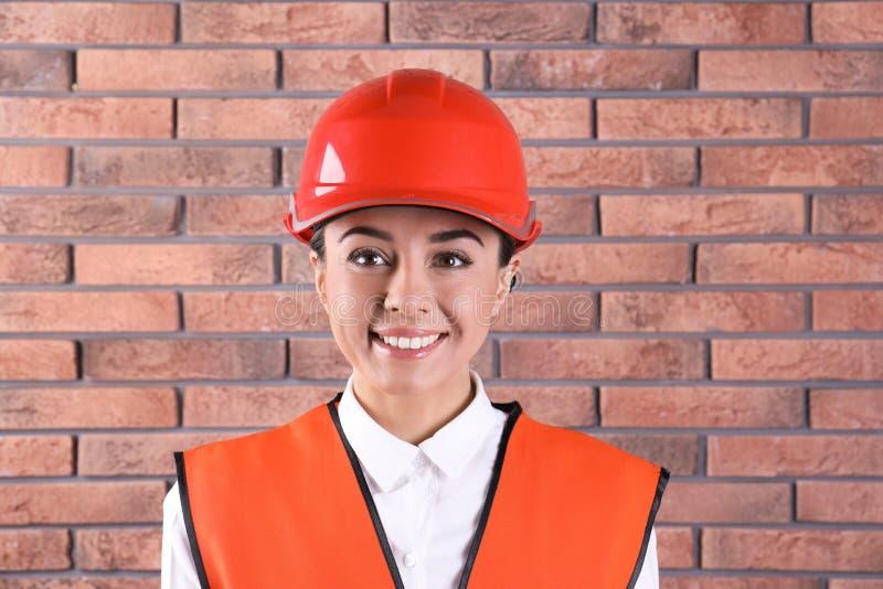 Weiblicher Wirtschaftsingenieur in der Uniform auf Backsteinmauerhintergrund stockfotos