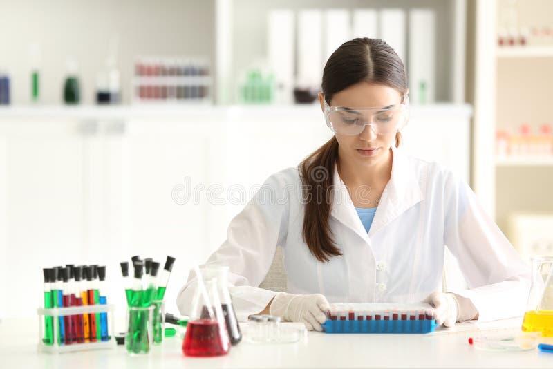 Weiblicher Wissenschaftler, der mit Blutproben im Labor arbeitet lizenzfreie stockfotos