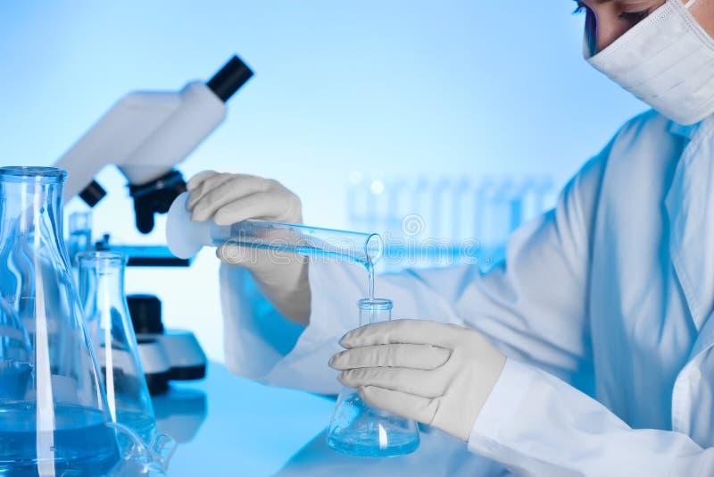Weiblicher Wissenschaftler, der mit Flüssigkeiten im Labor arbeitet lizenzfreie stockbilder