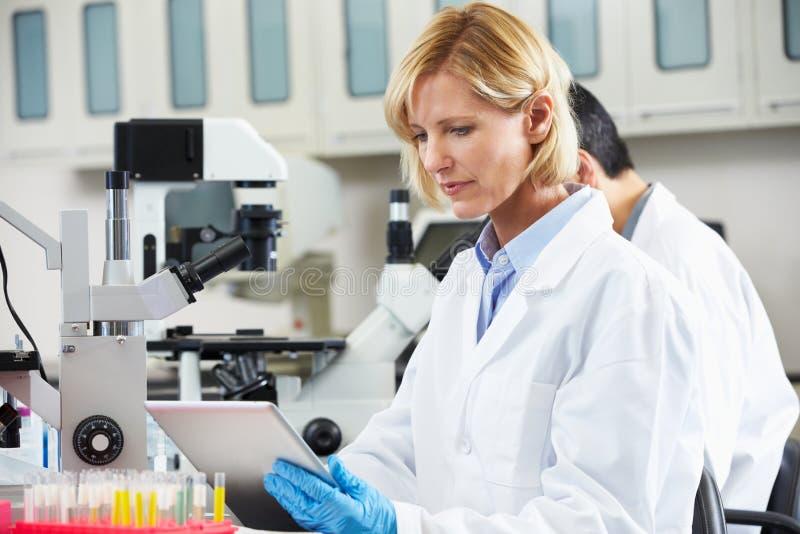 Weiblicher Wissenschaftler, der Tablette-Computer im Labor verwendet lizenzfreie stockbilder