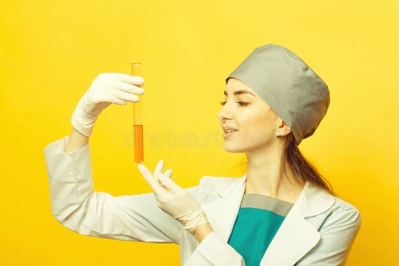 Weiblicher Wissenschaftler mit Flasche des chemischen Labors im Studio auf gelbem Hintergrund lizenzfreie stockfotos
