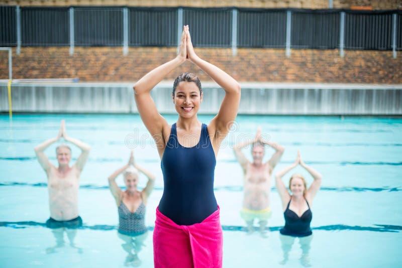 Weiblicher Yogalehrer, der ältere Schwimmer am Poolside unterstützt lizenzfreie stockfotos