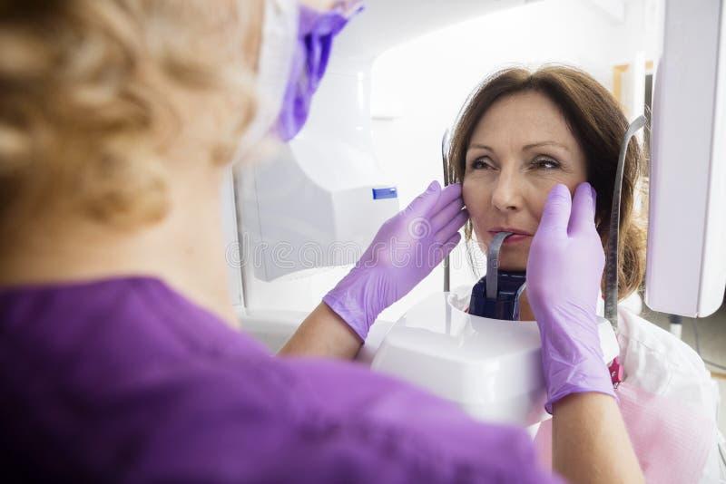 Weiblicher Zahnarzt Adjusting Patient u. x27; S-Gesicht auf Röntgenmaschine lizenzfreies stockfoto