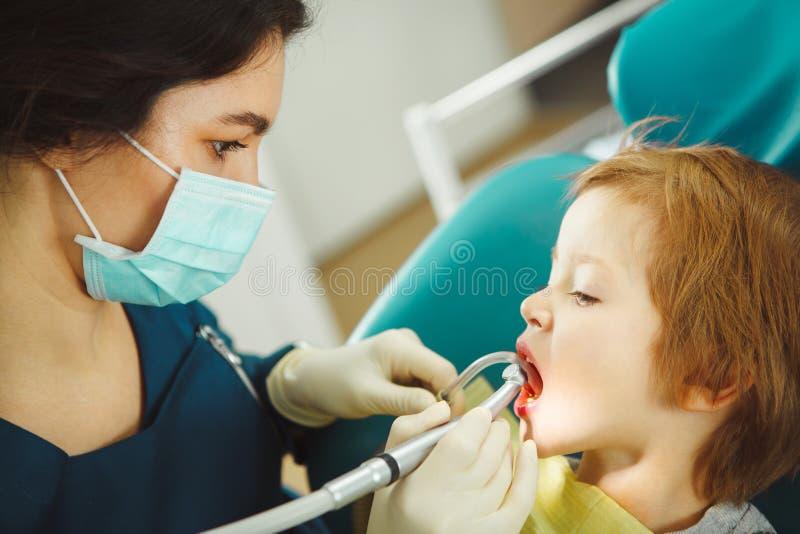 Weiblicher Zahnarzt bohrt die Zähne des kleinen Kindes Verhinderung des Zahnverfalls stockbilder