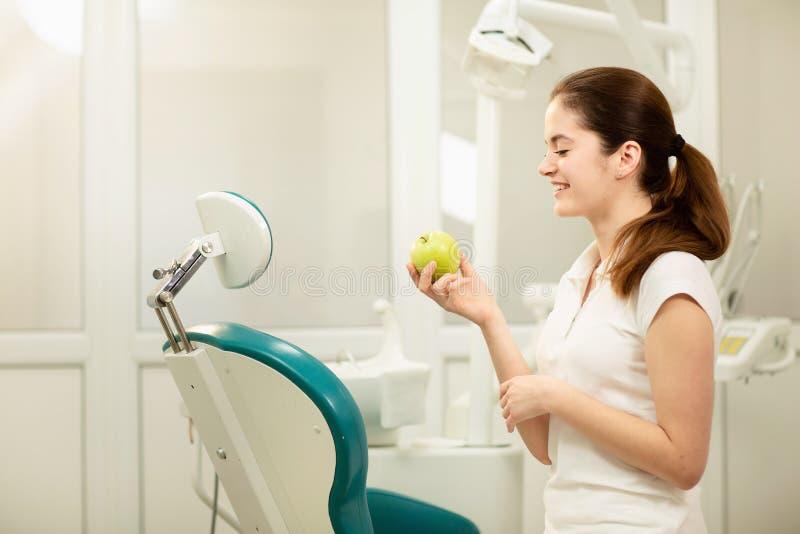 Weiblicher Zahnarzt, der einen grünen Apfel, einen Zahnpflegen und ein Verhinderungskonzept lächelt und hält lizenzfreie stockfotos
