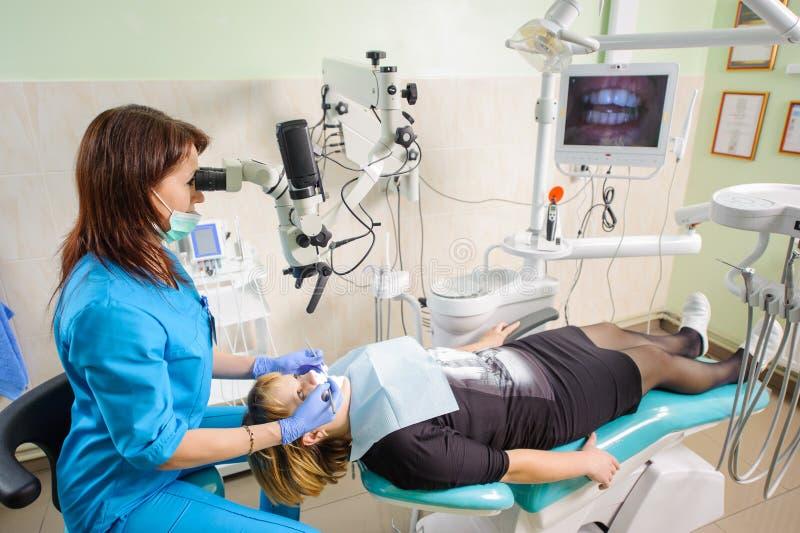 Weiblicher Zahnarzt, der mit Mikroskop an der modernen Zahnarztklinik arbeitet stockfoto