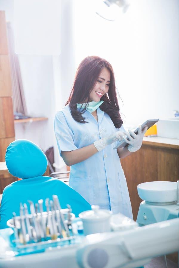 Weiblicher Zahnarzt mit Tablette über Klinik des Ärztlichen Diensts lizenzfreie stockbilder