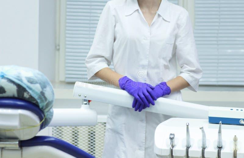 Weiblicher Zahnarzt ohne ein Gesicht nahe ihrem Arbeitsplatz stockfoto