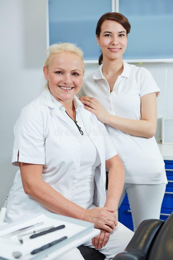 Weiblicher Zahnarzt und Zahnarzthelfer lizenzfreie stockbilder