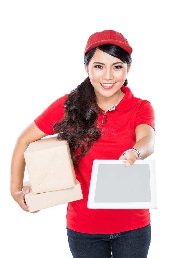 Weiblicher Zustelldienst, der glücklich Paket an Kostüm liefert lizenzfreie stockbilder