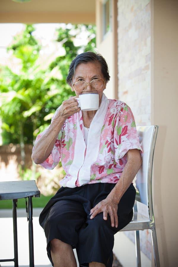 Weibliches älteres Sitzen in der Hauptterrasse und in trinkendem Heißgetränk stockfoto