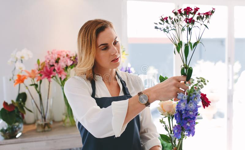 Weibliches Arbeiten am Blumenladen, der Blumen vereinbart stockfotos