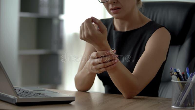 Weibliches Arbeiten an Laptop, glaubende Handgelenkschmerz, Arthrose, gemeinsame Entzündung stockfotos