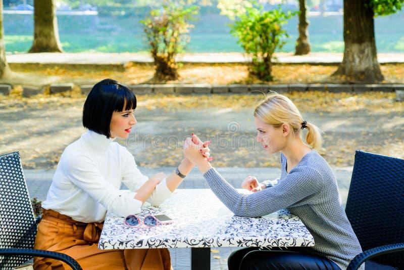 Weibliches Armwrestling zwei Frauen konkurrieren im Café Partnerschafts-Verh?ltnis-Konzept Herausforderung zwischen jungen Mädche stockfoto