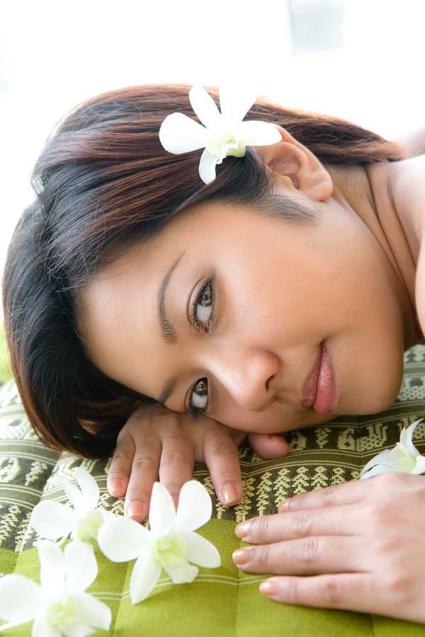 Weibliches asiatisches Stillstehen auf Massagebett stockfotos