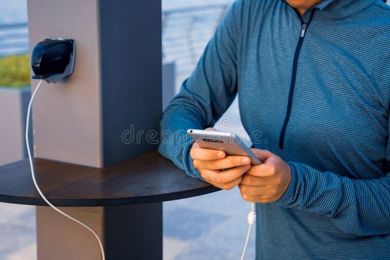 Weibliches Aufladungstelefon auf einem allgemeinen Ladegerät lizenzfreies stockfoto