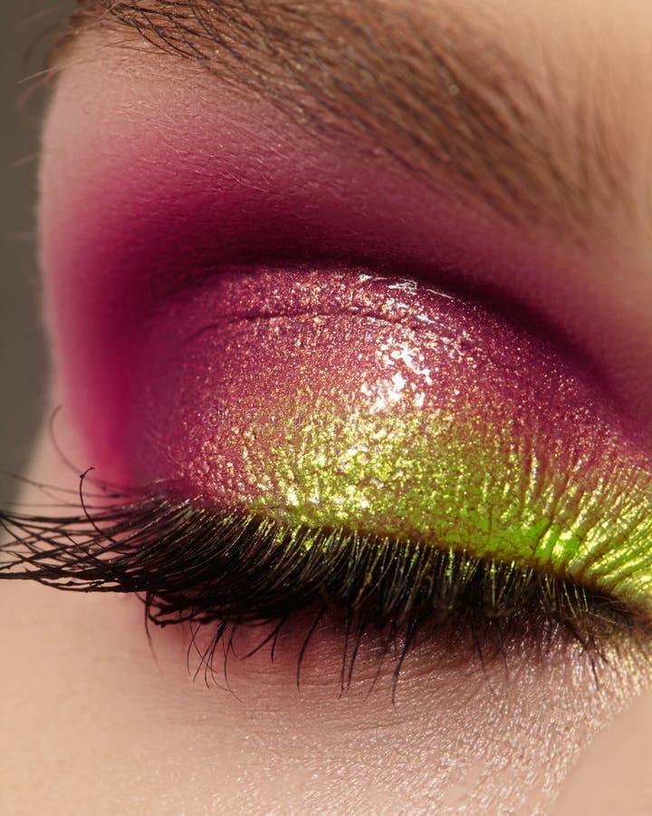 Weibliches Auge der Nahaufnahme mit hellem Make-up der schönen Mode Schöner glänzender purpurroter, grüner Lidschatten, machte Fu stockbild