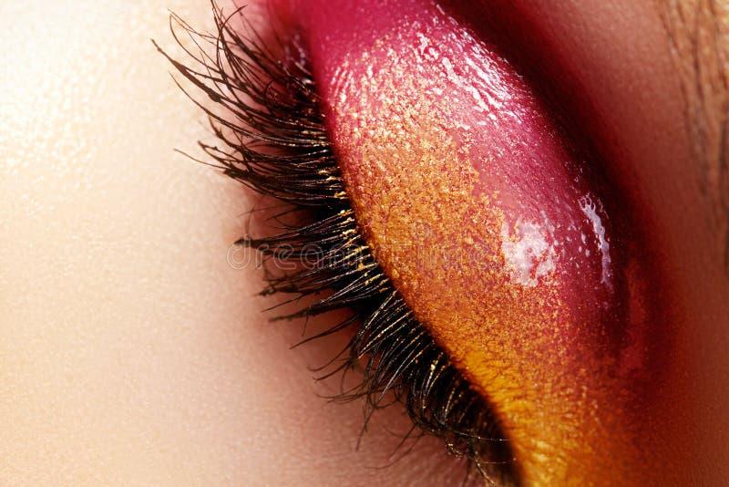 Weibliches Auge der Nahaufnahme mit hellem Make-up der schönen Mode Schönes glänzendes Gold, rosa Lidschatten, machte Funkeln nas lizenzfreie stockfotos