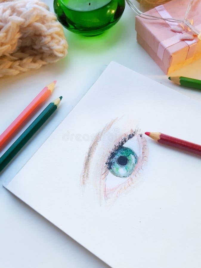 Weibliches Auge gezogene bunte pensils umgeben mit gemütlichen Gegenständen stockfotos