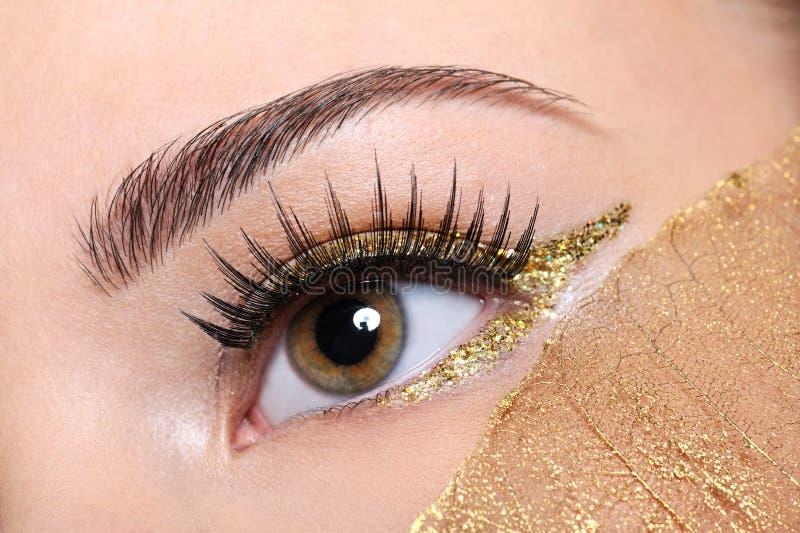 Weibliches Auge mit den falschen Wimpern und goldener Verfassung stockfotos