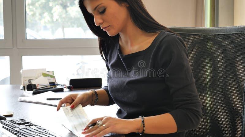 Weibliches Büroangestelltschreiben und unterzeichnende Kontrolle stockfoto