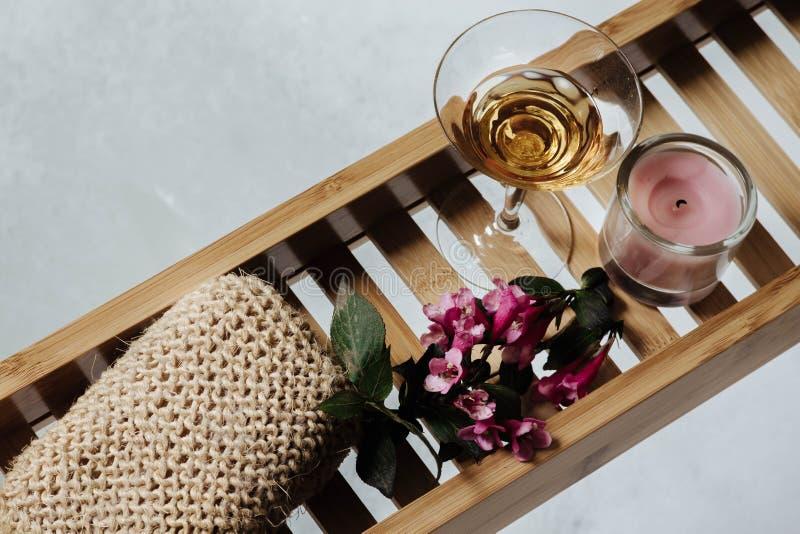 Weibliches Badezimmer - romantisches Bad mit natürlichem Bimsstein, Glas Weißwein, rosa Blumen und Kerze auf Regal für eine Badew lizenzfreie stockbilder