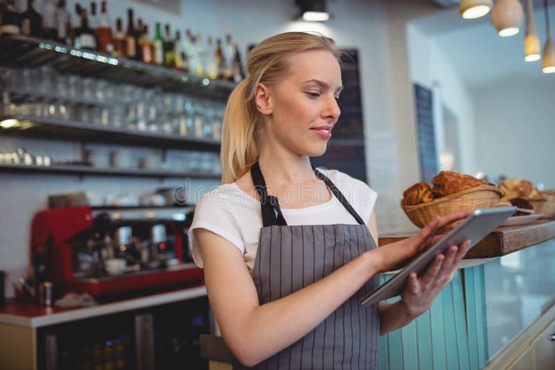 Weibliches barista unter Verwendung der digitalen Tablette an der Kaffeestube stockbild