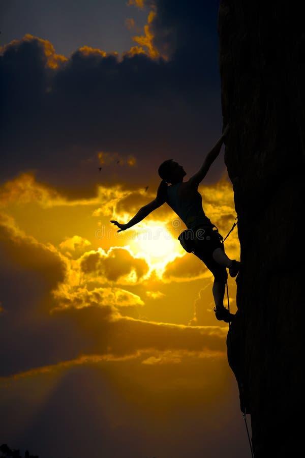 Weibliches Bergsteigerschattenbild und Sonnenuntergangwolkenhimmel lizenzfreies stockfoto