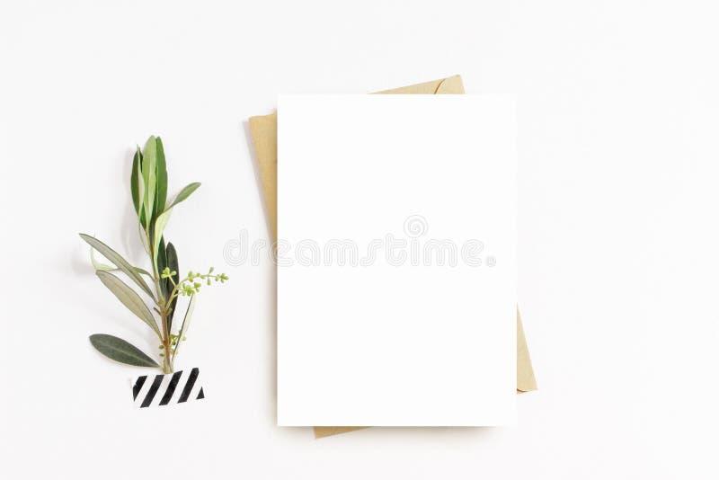 Weibliches Briefpapier, Tischplattenmodellszene Leere Grußkarte, Handwerksumschlag, washi Band und mit Ölzweig weiß stockbilder