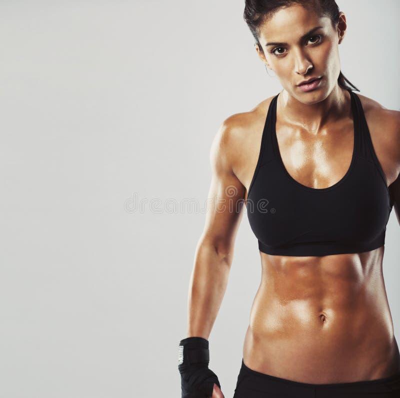 Weibliches Eignungsmodell auf grauem Hintergrund lizenzfreies stockfoto