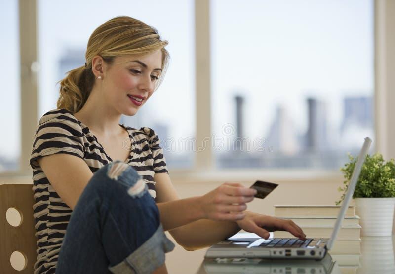 Weibliches Einkaufen online vom Haus stockfotografie