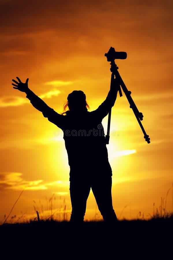 Weibliches Fotografschattenbild an der untergehenden Sonne lizenzfreie stockfotos