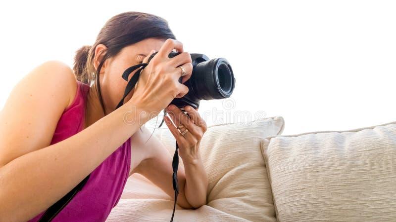 Weibliches Fotografschießen auf einem Sofa auf weißem Hintergrund lizenzfreie stockbilder