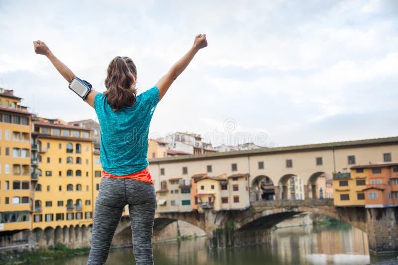 Weibliches Freuen der Eignung vor Ponte Vecchio, Italien lizenzfreie stockbilder
