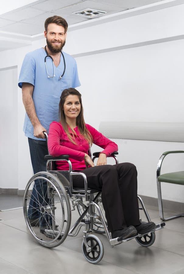 Weibliches geduldiges Sitzen im Rollstuhl während Krankenschwester Standing At Hos lizenzfreies stockbild