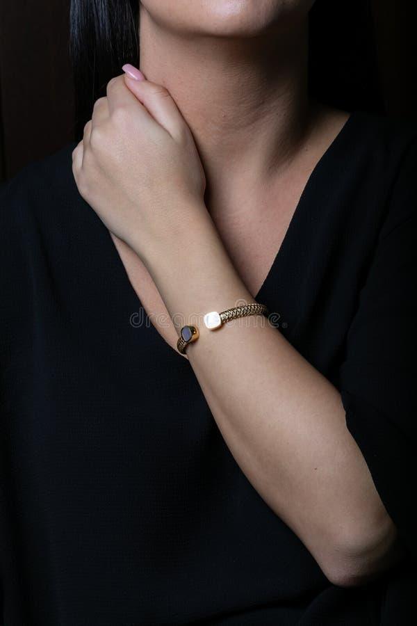 Weibliches, gelbes Goldweidenarmband mit Steinen in der Mitte, in Form eines Quadrats an Hand, auf einem schwarzen Hintergrund stockfotografie