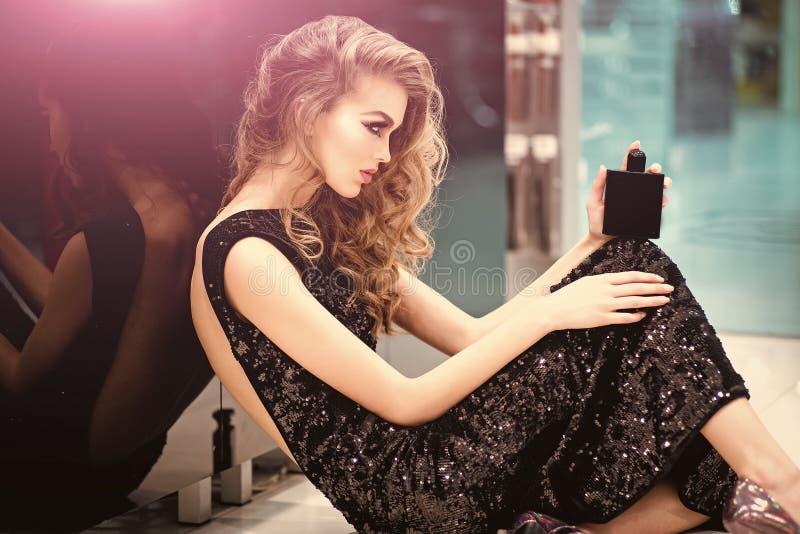 Weibliches Gesicht Fragen, die Mädchen beeinflussen Parfümflasche in den Händen der sinnlichen Frau, Parfümerie lizenzfreie stockfotos