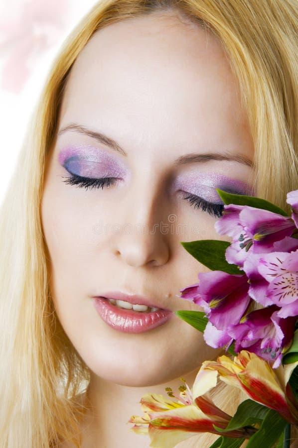 Weibliches Gesicht mit gesunder Haut und Blumen lizenzfreies stockbild