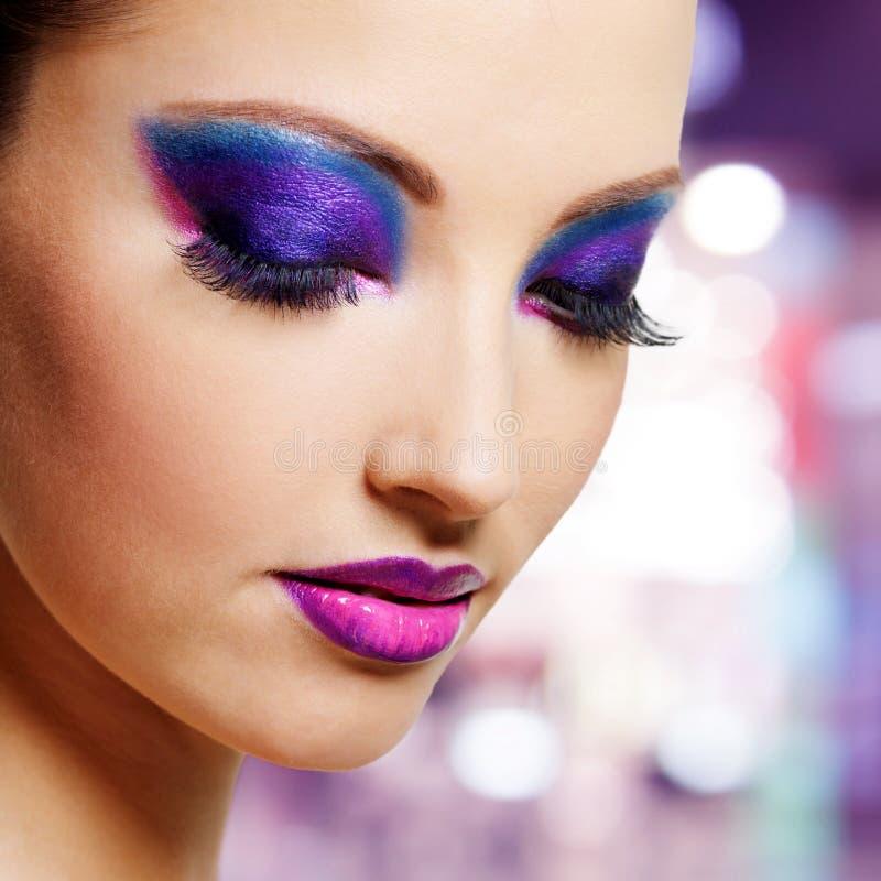 Weibliches Gesicht mit purpurrotem Modemake-up stockbilder