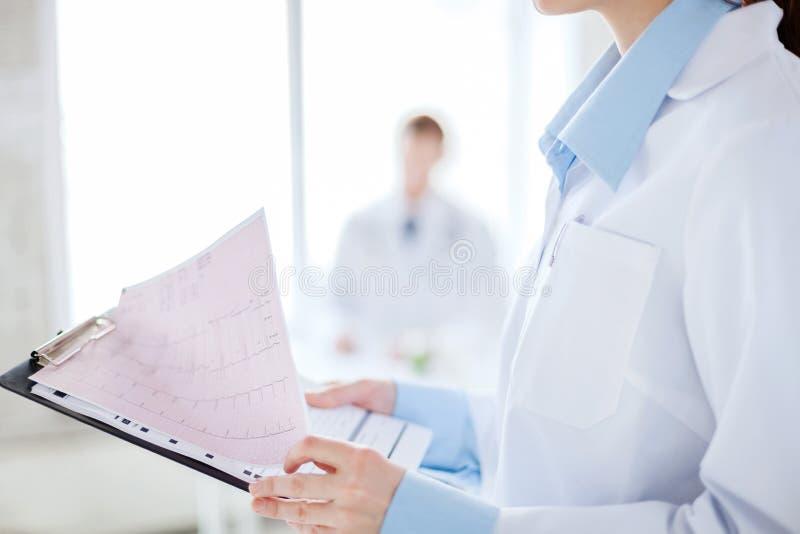 Weibliches haltenes Klemmbrett mit Kardiogramm lizenzfreie stockfotografie
