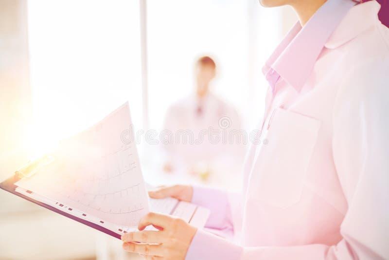 Weibliches haltenes Klemmbrett mit Kardiogramm stockfotografie