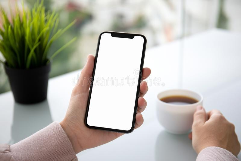 Weibliches Handholding-Notentelefon mit lokalisiertem Schirm über der Tabelle im Café lizenzfreie stockfotografie
