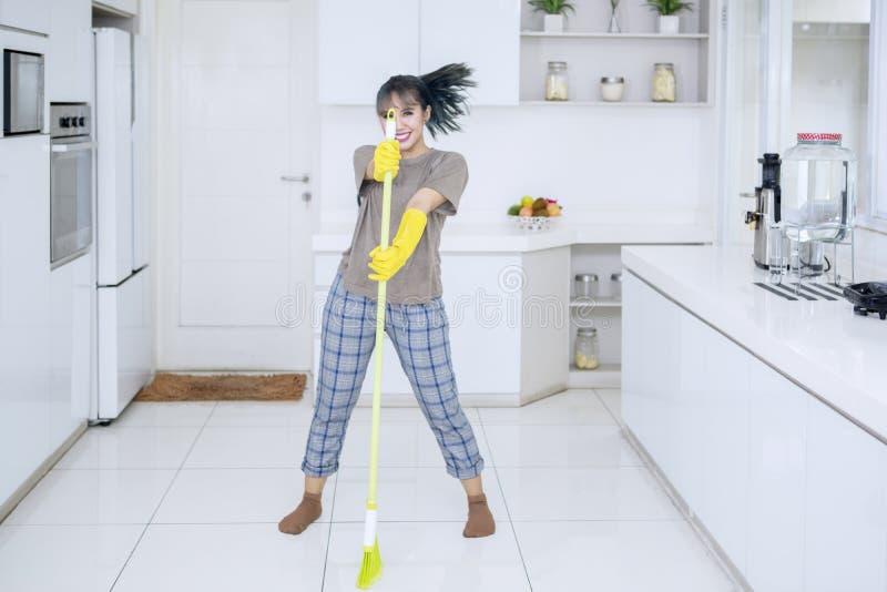 Weibliches Haushälterintanzen mit einem Besen stockfoto