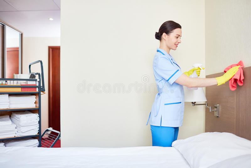 weibliches Haushaltungsarbeitskraftmädchen, das Bett mit Bettzeug am Gasthausraum macht lizenzfreie stockfotos