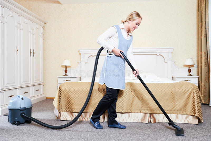 weibliches Haushaltungsarbeitskraftmädchen, das Bett mit Bettzeug am Gasthausraum macht weibliche Haushaltungsarbeitskraft mit St stockfotos