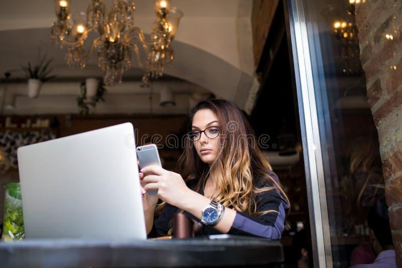 Weibliches Hochschulstudentgrasen wifi über Mobiltelefon während der on-line-Ausbildung stockfotos