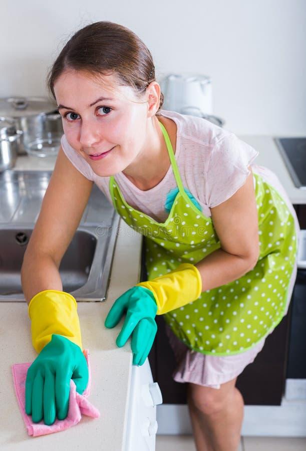 Weibliches houseworker mit Lappen und Reiniger zuhause lizenzfreie stockfotografie