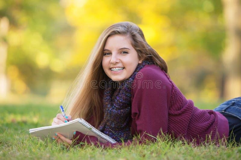 Weibliches jugendlich auf dem Boden Studieren lizenzfreie stockfotos