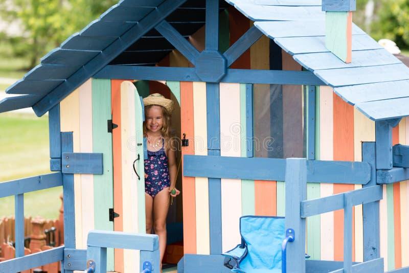 Weibliches Kind, das an der Tür wenigen Hauses steht lizenzfreie stockbilder