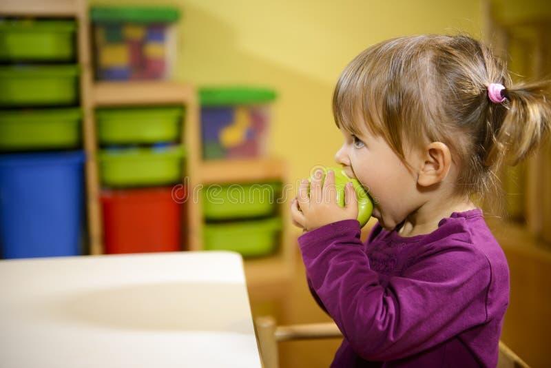Weibliches Kind, das grünen Apfel im Kindergarten isst lizenzfreie stockfotos